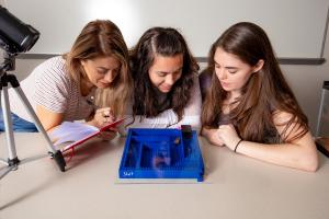 Three female students studying roach behavior using maze